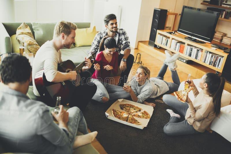 Jongeren die pizza eten en cider in de ruimte drinken royalty-vrije stock foto's