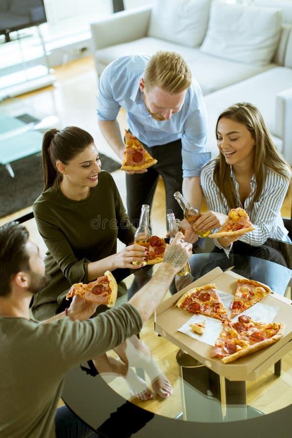 Jongeren die pizza eten en cider in het moderne binnenland drinken stock afbeelding
