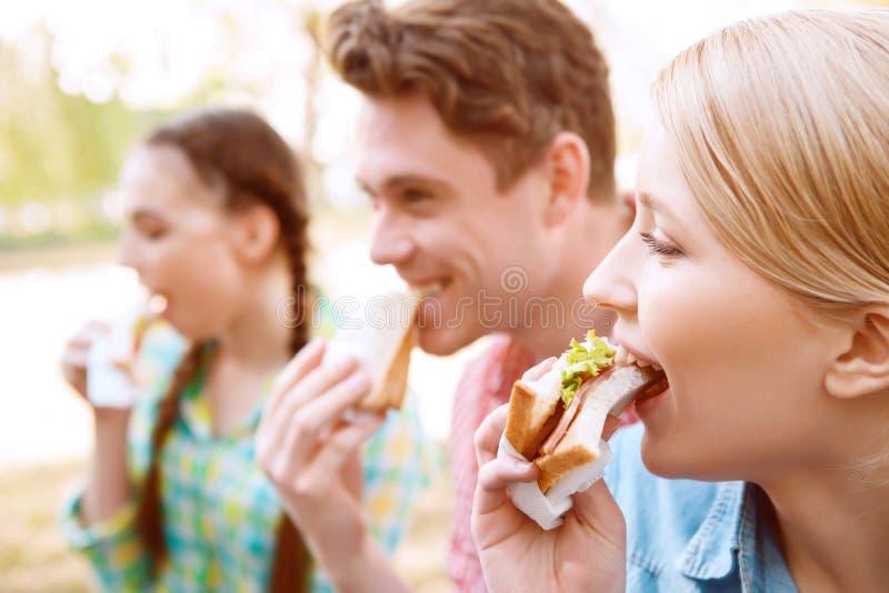 Jongeren die sandwiches eten tijdens picknick stock fotografie