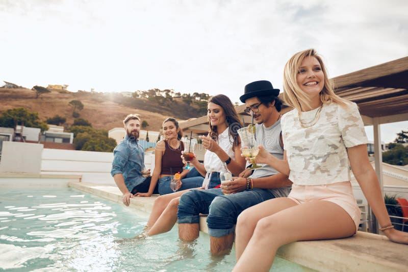 Jongeren die uit door zwembad hangen royalty-vrije stock fotografie
