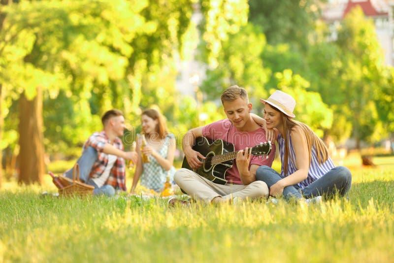 Jongeren die van picknick in park genieten royalty-vrije stock foto's