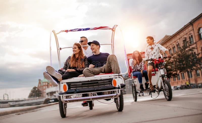 Jongeren die van rit met drie wielen in de stad genieten royalty-vrije stock afbeeldingen