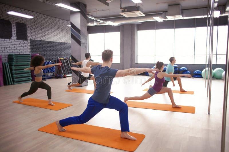 Jongeren die yoga in gymnastiek doen stock foto