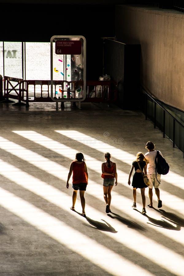 4 jongeren loopt naar de uitgang van de Turbinezaal, Tate Modern, Londen royalty-vrije stock foto's