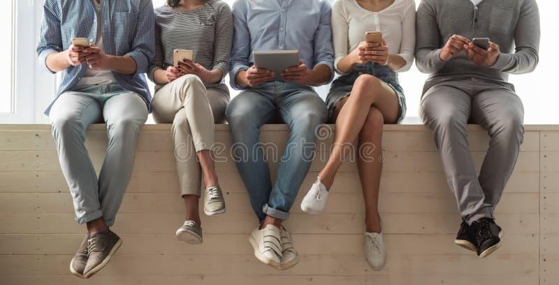 Jongeren met gadgets stock afbeeldingen