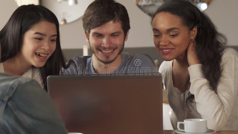 Jongerengolf hun handen aan het laptop scherm bij de koffie stock afbeelding
