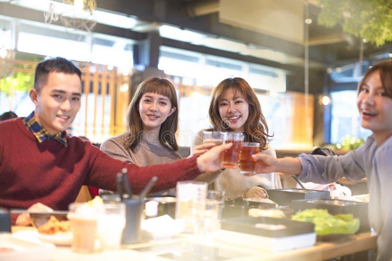Jongerenvrienden die en in het restaurant roosteren eten royalty-vrije stock foto's