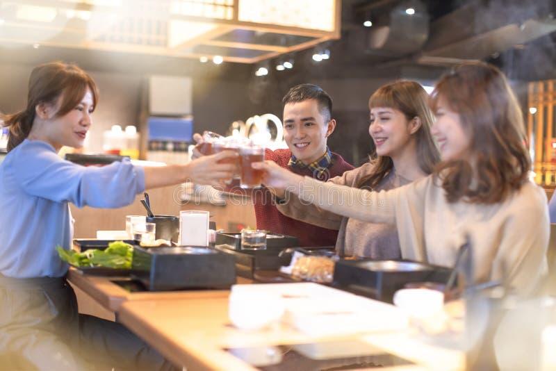 Jongerenvrienden die en in het restaurant roosteren eten stock afbeelding