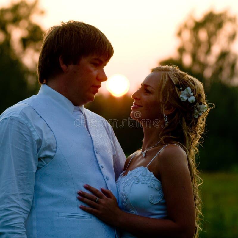 Jonggehuwden bij zonsondergang stock fotografie