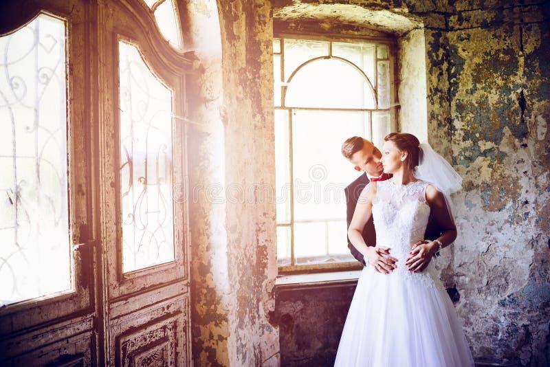 Jonggehuwden die bij de deur in een oud huis koesteren royalty-vrije stock foto
