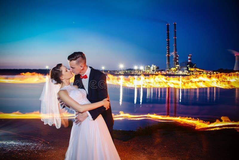 Jonggehuwden die dichtbij 's nachts meer kussen royalty-vrije stock foto