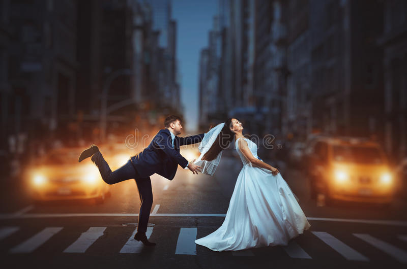 Jonggehuwden die een straat van de nachtstad kruisen royalty-vrije stock foto's