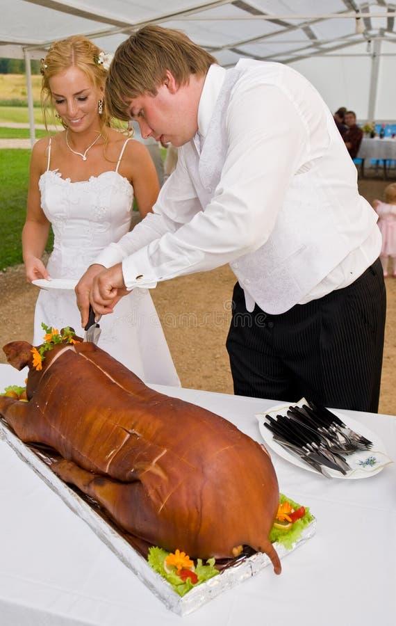 Jonggehuwden die geheel varken snijden stock fotografie