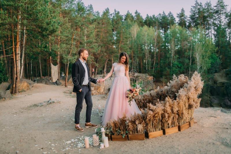 Jonggehuwden die handen, lach en glimlach, gelukkige en blije ogenblik houden De bruidegom kijkt op zijn mooie bruid outdoors stock fotografie