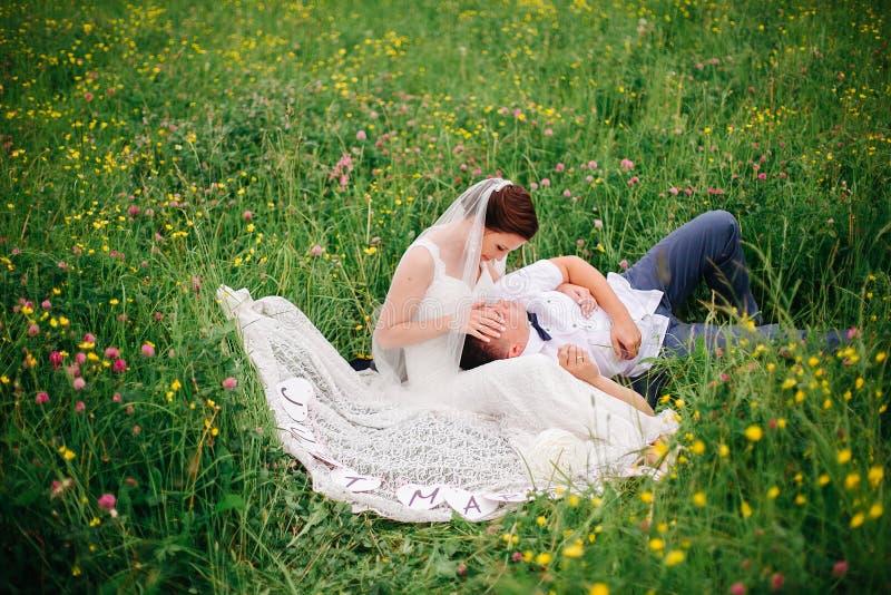 Jonggehuwden die op het weidehoogtepunt liggen van bloemen stock foto