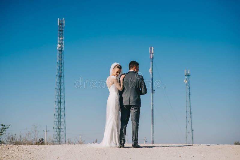 Jonggehuwden die passionately terwijl status op de weg kussen stock foto