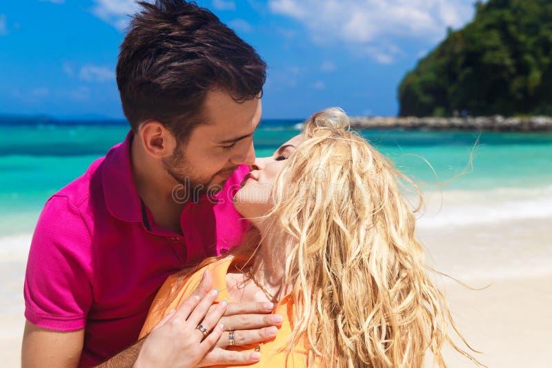 Jonggehuwden die pret op een tropisch strand hebben honeymoon stock afbeelding