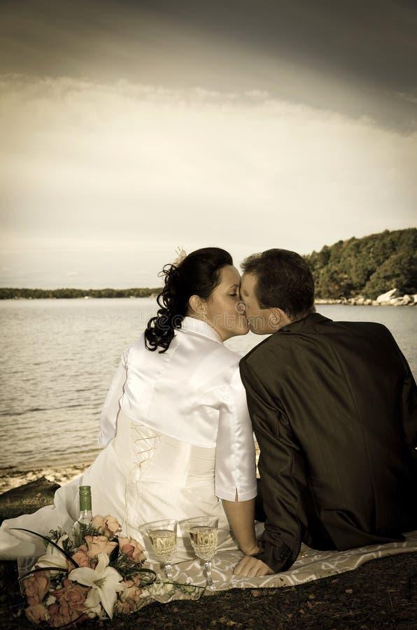 Jonggehuwden die in retro stijl kussen stock foto