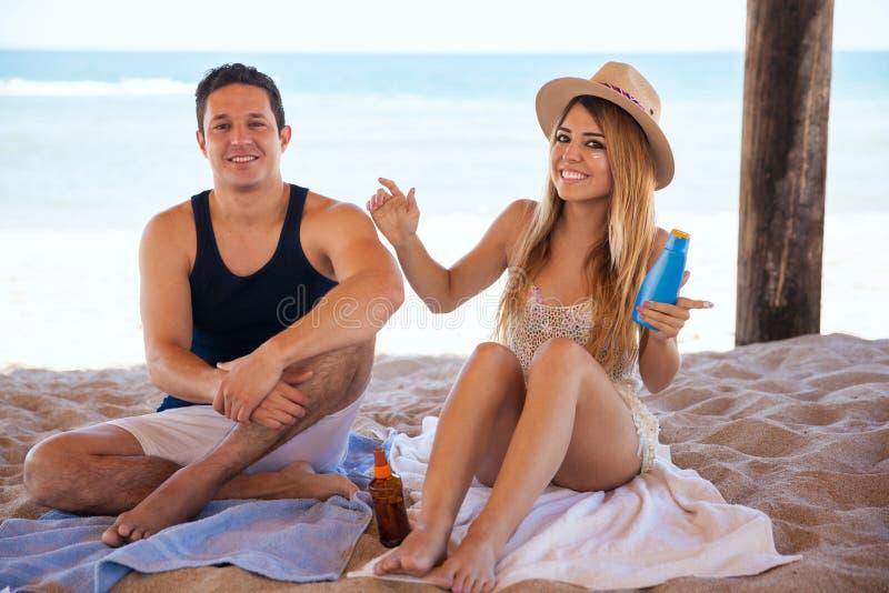 Jonggehuwden die sunblock bij het strand aanzetten royalty-vrije stock afbeeldingen