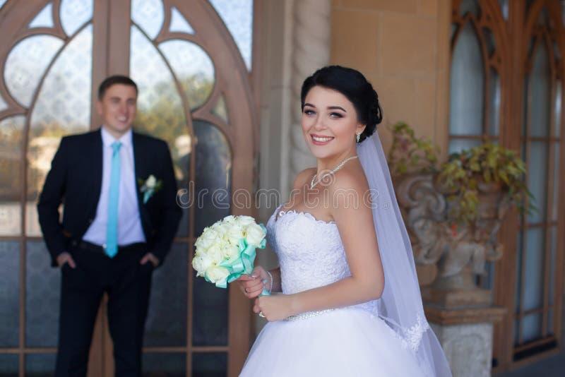 Jonggehuwden die tegen de retro deur stellen stock afbeeldingen
