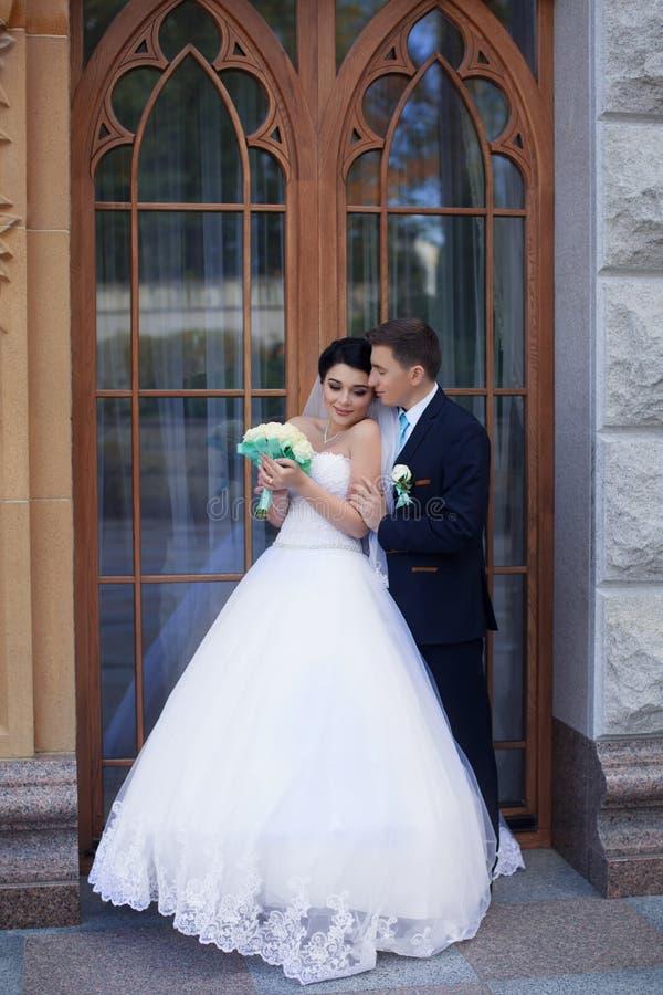 Jonggehuwden die tegen de retro deur stellen royalty-vrije stock afbeelding