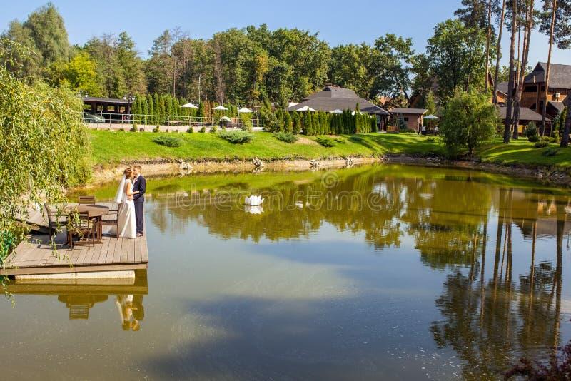 Jonggehuwden die terwijl status op houten pijler dichtbij meer bij zon koesteren stock fotografie