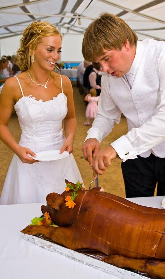 Jonggehuwden die varken snijden royalty-vrije stock afbeelding