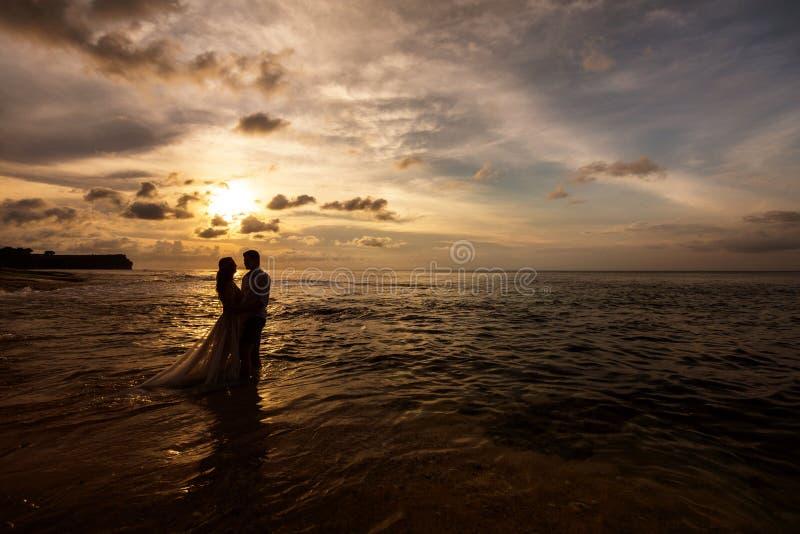 Jonggehuwden op het strand bij zonsondergang stock foto's