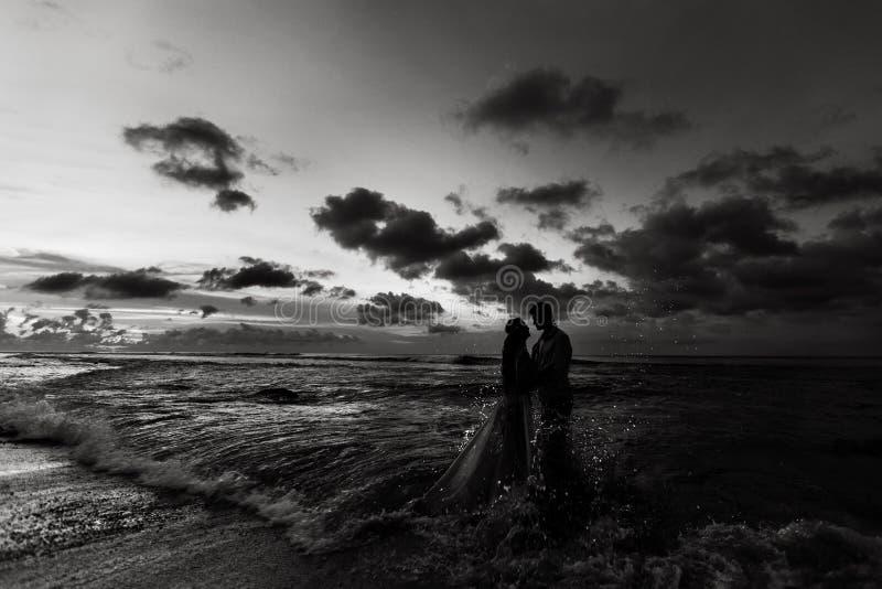 Jonggehuwden op het strand bij zonsondergang stock afbeelding