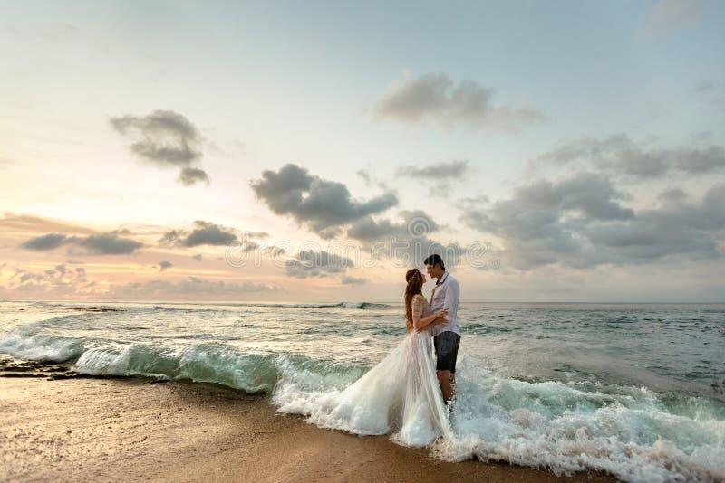 Jonggehuwden op het strand bij zonsondergang royalty-vrije stock foto