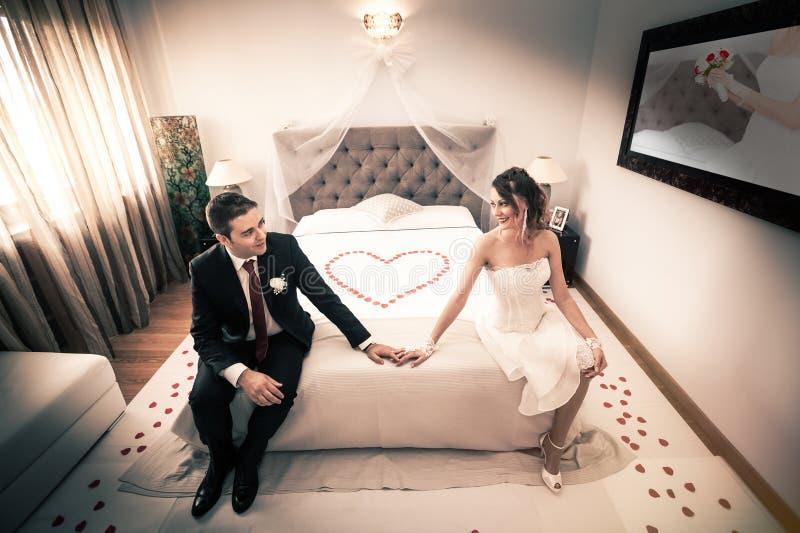 Jonggehuwden in slaapkamer met hart stock afbeeldingen