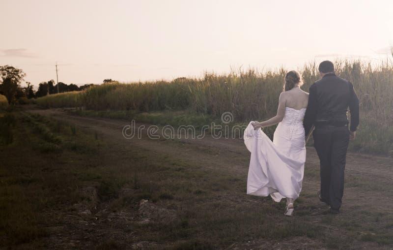 Jonggehuwdepaar bij zonsondergang royalty-vrije stock afbeelding