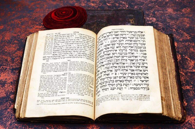 Joodse Bijbel Een open, oud Joods boek en een rode, gebreide joodse bale Torah in het Hebreeuws en Aramaisch Sluiting van de Hebr stock fotografie