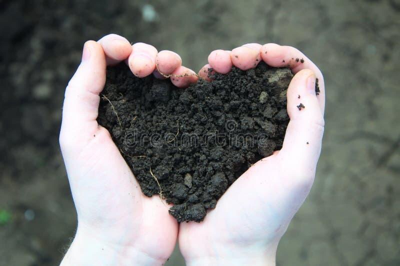 Jord för handinnehavsvart i form av hjärta royaltyfria foton