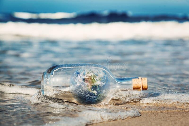 Jord i flaskan som kommer med vågen från havet Miljö rent världsmeddelande royaltyfria foton