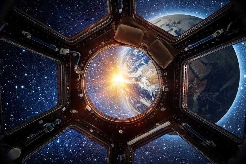 Jord och galax i rymdskeppinternationella rymdstationenfönster fotografering för bildbyråer