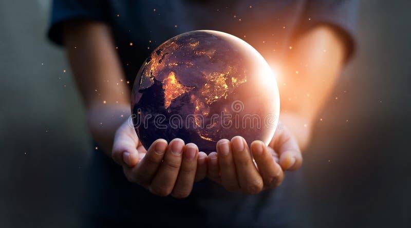 Jord på natten rymde i mänskliga händer brown räknad dagjord som miljölövverk går den gående gröna treen för text för slogan för  royaltyfria foton