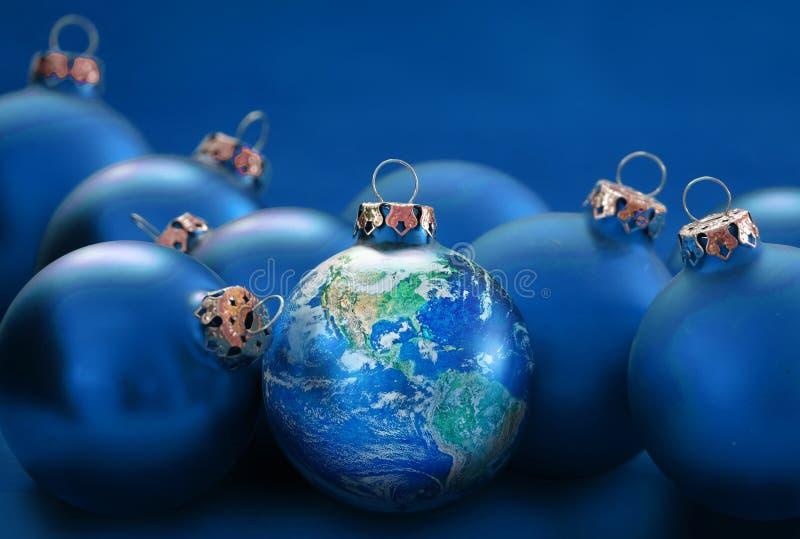 Jorda en kontakt jordklotet, som jul klumpa ihop sig mellan blåa struntsaker, metafor uni royaltyfria bilder