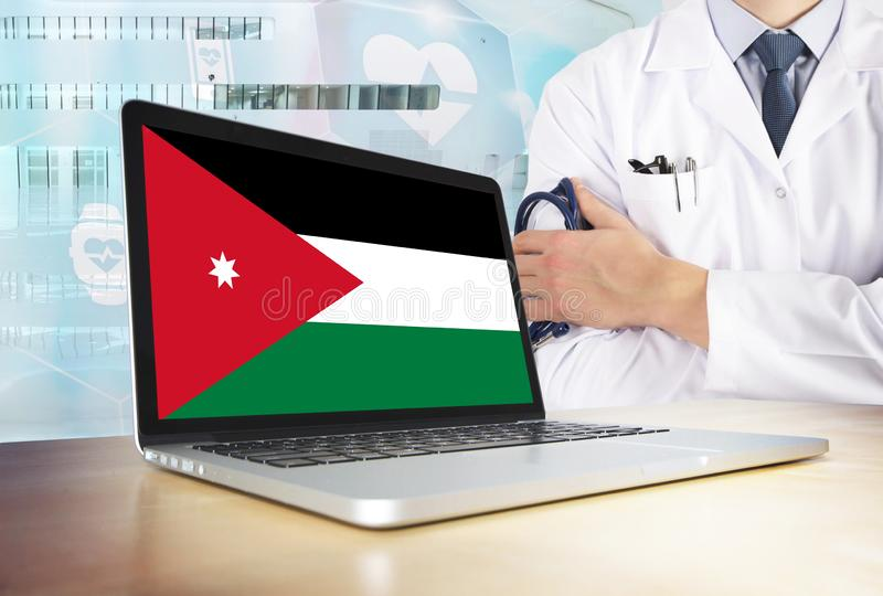 Jordan healthcare system in tech theme. Jordanian flag on computer screen. Doctor standing with stethoscope in hospital. Cryptocurrency and Blockchain concept royalty free stock photos