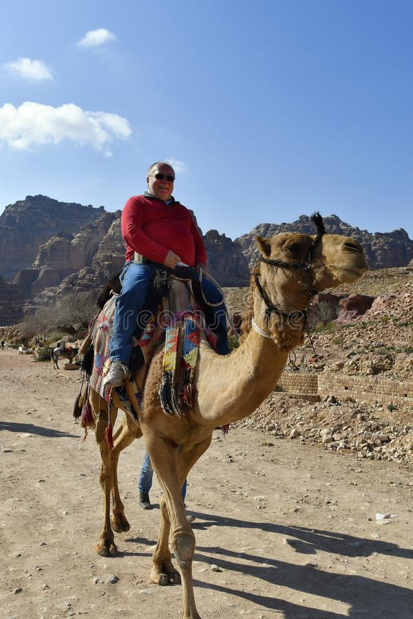 Jordan, Middle East, Ancient Petra. Petra, Jordan - March 06, 2019: Unidentified tourist riding a camel in ancient Petra, a UNESCO World heritage site in Middle royalty free stock image