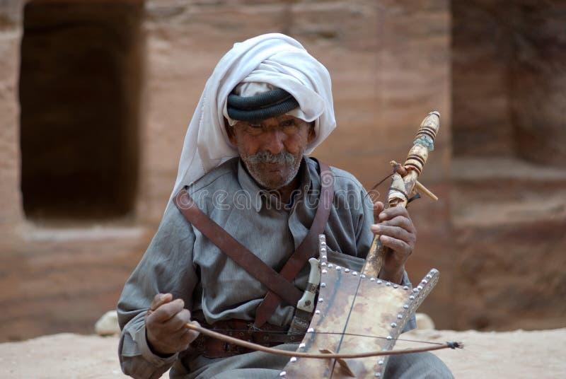 jordan petra Beduinman som spelar det traditionella instrumentet arkivfoton