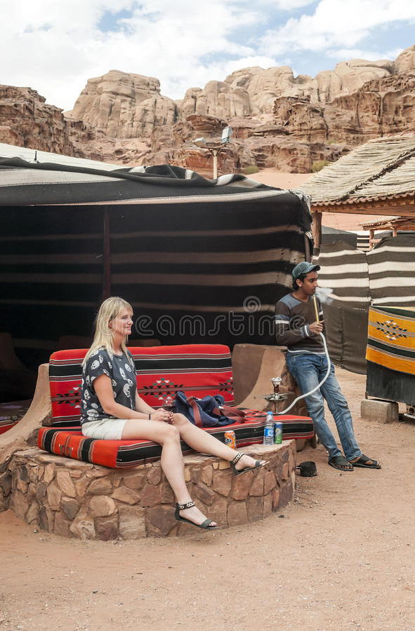 Jordanian man smoking a pipe. With a European woman in the desert of Wadi Rum in Jordan on a sunny day, it is an editorial vertical image royalty free stock photo
