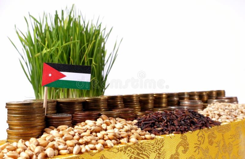 Jordanienflagga som vinkar med bunten av pengarmynt och högar av vete arkivbild