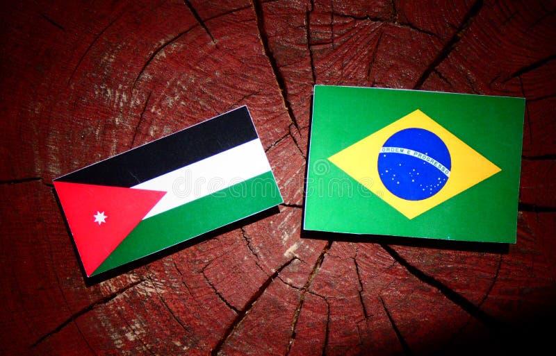 Jordansk flagga med den brasilianska flaggan på en isolerad trädstubbe royaltyfria bilder