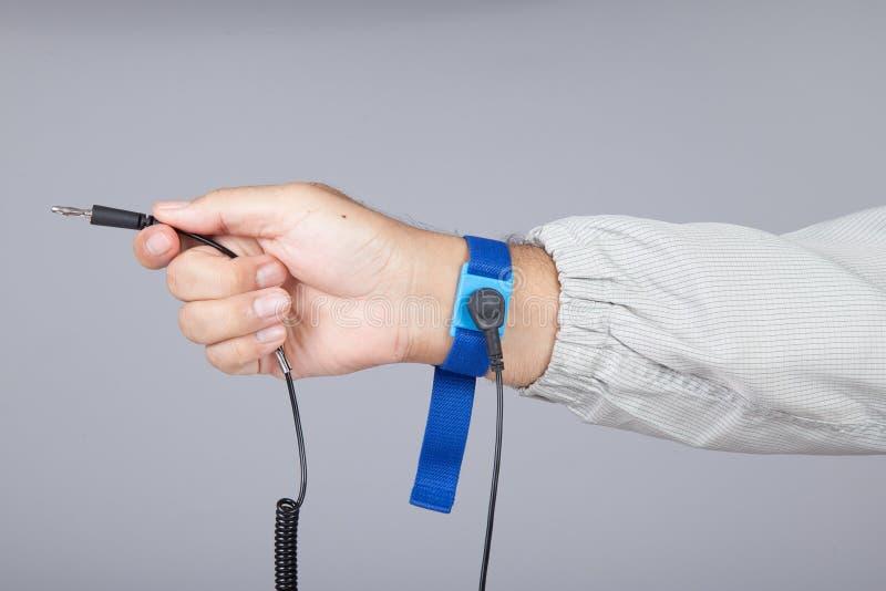 Jordarmband på manhanden som bär grå bakgrund för ESD-torkduk A arkivfoto