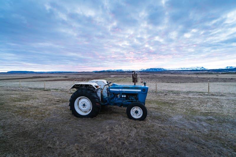 Jordbruksöversikt En liten traktor på ett fält under solnedgången Jordbruk på Island, Skandinavien arkivfoton