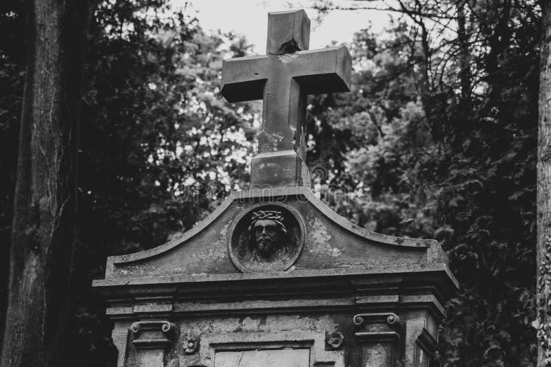 Jordfästningvalv i kyrkogården, ett stort stenkors, bilden av Jesus på jordfästningvalvet arkivfoton