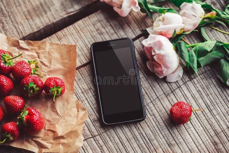 Jordgubbar, blommor och telefon på den lantliga tabellen Sund frukost, rengöring som äter, strikt vegetarianmatbegrepp royaltyfri fotografi