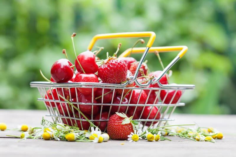 Jordgubbar för körsbär för nya frukter för sommarskörd i shoppingkorg Fält för grunt djup, selektiv fokus, trätabell royaltyfria bilder