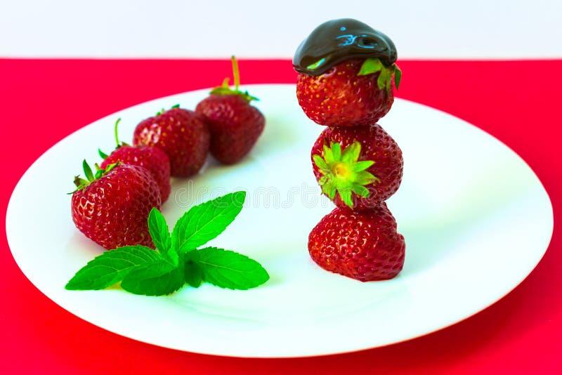 Jordgubbar i choklad och mintkaramell på en vit platta R?d bakgrund arkivfoto